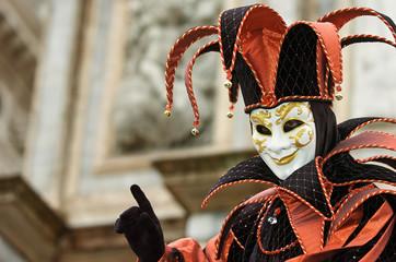 Person in Venetian costume attends the Carnival of Venice.