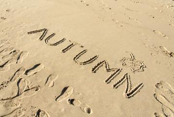 Word autumn handwritten and leaf drawn in sand