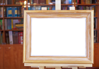 white canvas of wood picture frame on easel in library