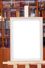 white canvas of simple picture frame on easel in library