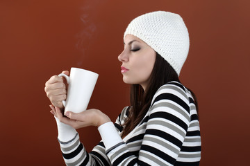 beautiful girl with cup in hands to keep warm drink