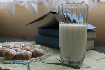 Glass of milk, homemade sweets and pile of books