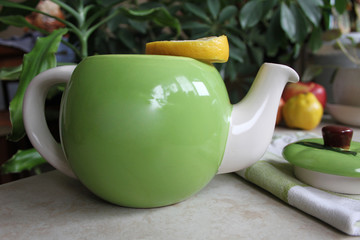 Still life with green kettle and piece of lemon