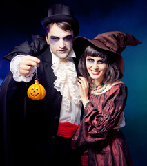 Man and woman wearing as vampire and witch. Carnival. fog.