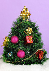 Decorated artificial Christmas Tree on lilac background