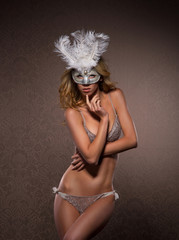 A young and sexy woman posing in a white Venetian mask