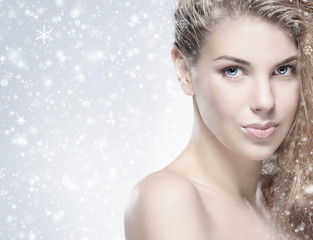 Portrait of a young and naked woman on a snowy background