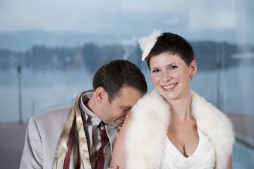 Brautpaar lacht und der Bräutigam versteckt sich