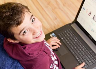 Freundlicher Junge -  Kind mit Notebook - Laptop auf dem Schoß