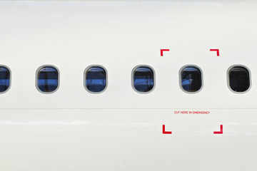 Windows of airplane with emergency sign.