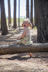 cute young girl playing in the woods