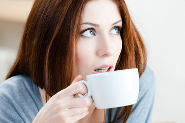 Woman with cup of tea has a rest at the bar