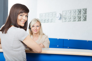 Young Woman With Receptionist At Dentist's Office