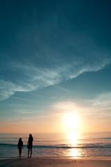 Girls on beautiful beach during sunset.