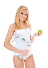 Attraktive junge Frau hält Personenwaage und Apfel