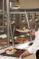 buffet self-service food display human hand take plate