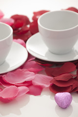 Coffee cup and rose petals