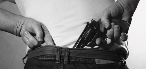 man  is hiding a gun at his back