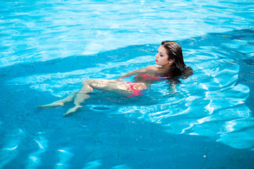 Beautiful woman floating in a swimming pool.