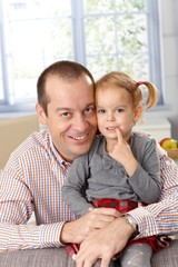 Happy father and daughter at home smiling