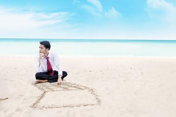 Businessman thinking on a beach