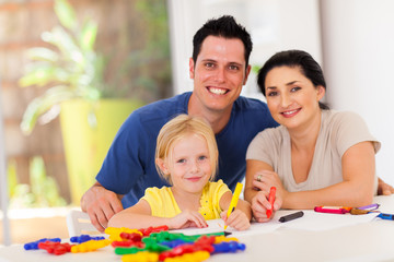happy parents and little daughter drawing pictures at home