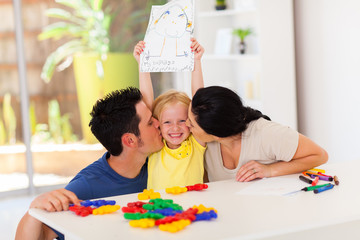 happy parents kissing cute little daughter with her drawing