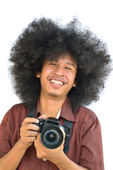 Smiling young man with long hair and holding digital camera