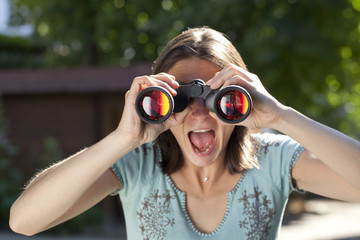 amazed woman looking through binoculars