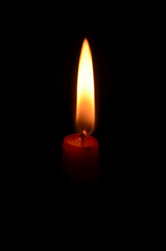 Burning red candle on black background