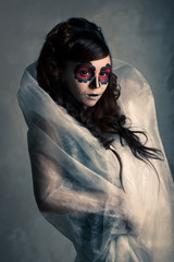 Portrait of young woman with sugar skull make-up . Dramatic ligh