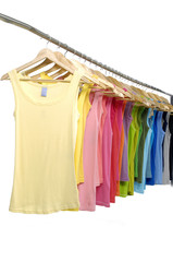 line of multi colorful shirts on hangers