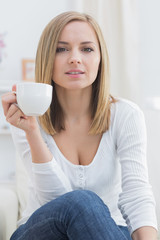 Young woman with coffee cup sitting on couch