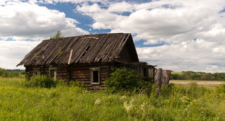 Old wooden cottage on the meadow near the forest