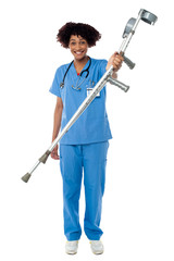 Lady doctor handing over crutches to the patient