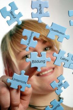 Junge Frau legt Puzzle-Teile zusammen zum Thema Ausbildung