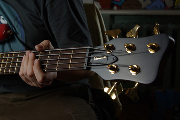 Playing an bass guitar with brown neck