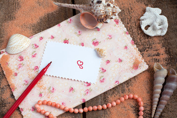 Saint Valentine's Love letter, shells and red felt pen in marine