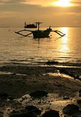 Bali fisherman boat over sunset at Tuban Beach, Bali