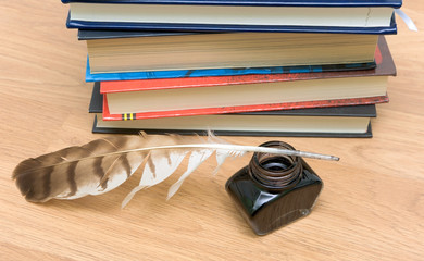 pen, ink and books on a wooden board