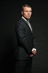 Fashion man wearing grey suit. Studio shot against black.