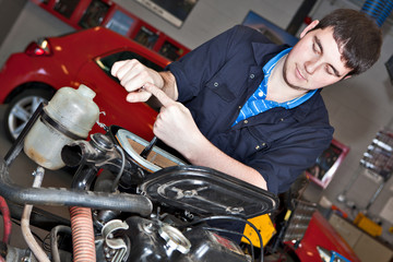 Man holding a spanner over a car engine