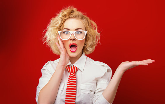 Surprised woman showing product, isolated on red background