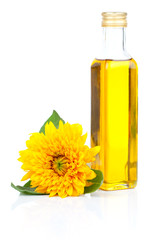 oil in glass bottle and sunflowers, isolated on white