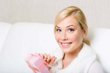 Happy woman in white sweater holds a gift