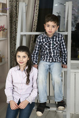 cute little boy and sister sitting on staircase
