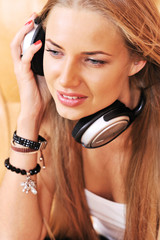 Young woman listen to music wearing headphones in the living roo