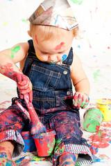 süßes kleines Kind in Latzhosen mit Pinseln und Farben