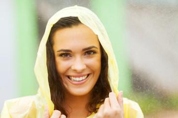 beautiful woman dress in raincoat in the rain