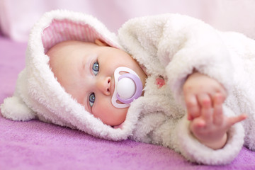 Cute baby girl with blue eyes in white fur lying with nipple